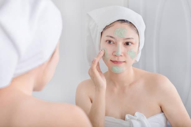 Frau Maske auf ihr Gesicht und Blick in den Spiegel – Foto