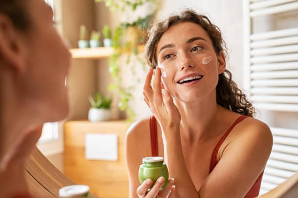 Woman applying moisturiser on face during morning routine stock photo
