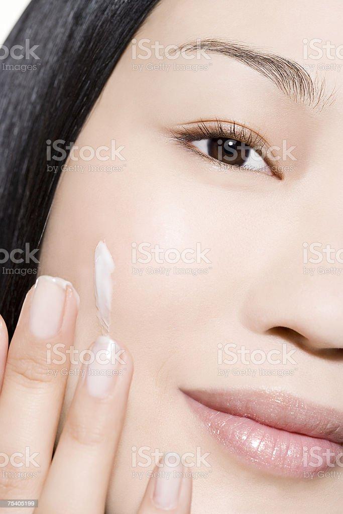 Woman applying moisturiser stock photo