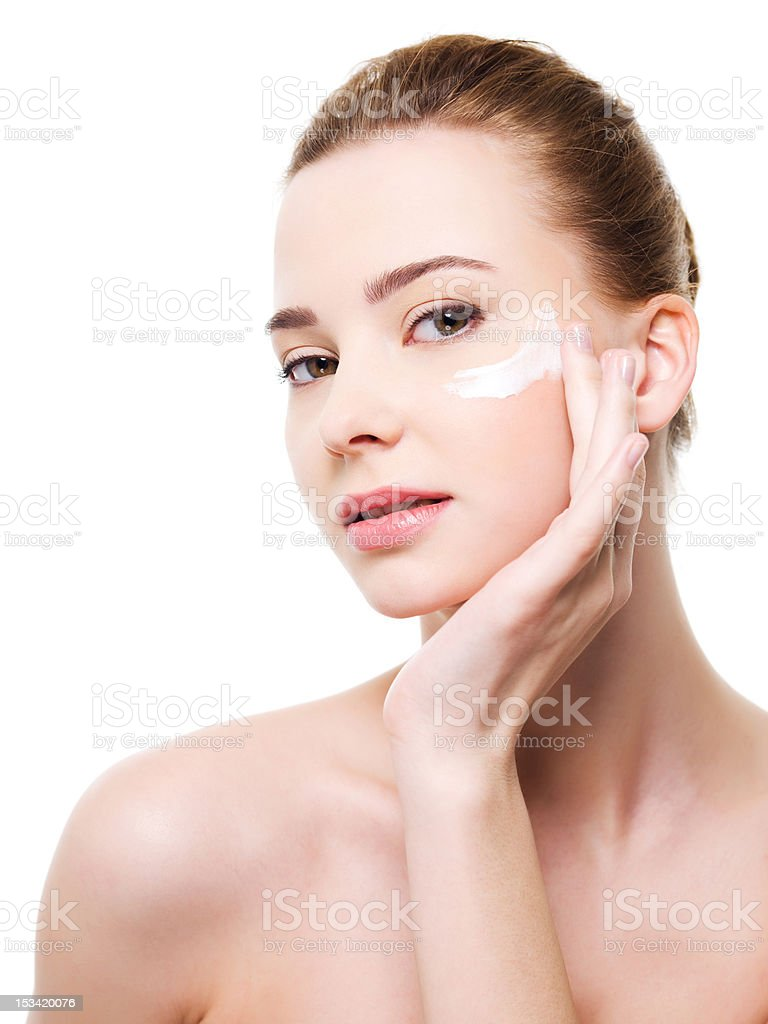 Woman applying moisturizer cosmetic under eyes stock photo