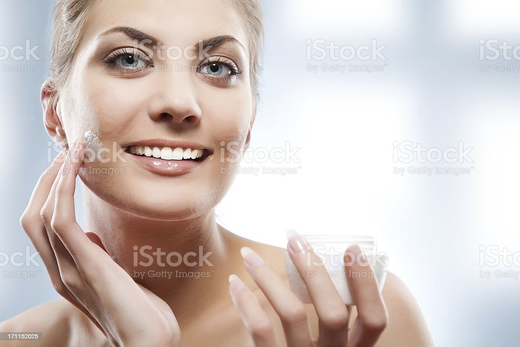 Woman applying moisturizer cream on face. royalty-free stock photo