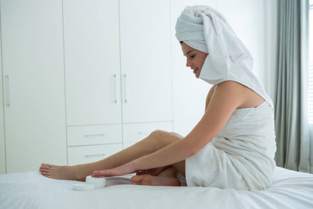 frau, die anwendung der feuchtigkeitscreme creme an ihrem bein im schlafzimmer - bein tag routine stock-fotos und bilder