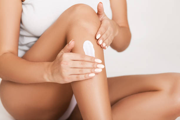 Woman applying moisturizer cream on her legs Woman applying moisturizer cream on her legs, white studio background lingerie stock pictures, royalty-free photos & images