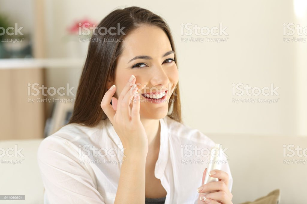Woman applying moisturizer cream on the face stock photo