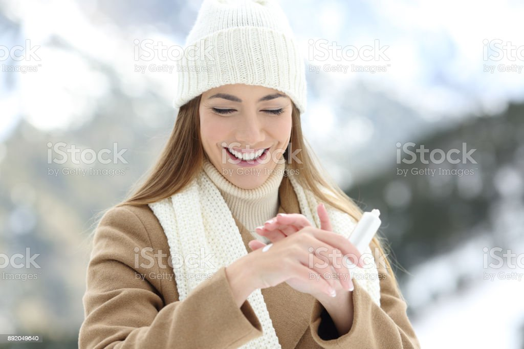 Woman applying moisturizer cream to hydrate hands stock photo