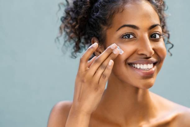 Woman applying moisturizer on face stock photo