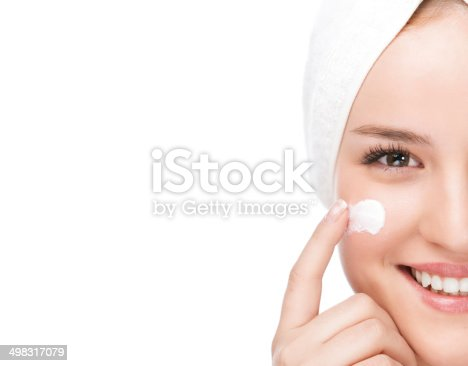 Close-up portrait of a beautiful woman applying moisturizer on her face.