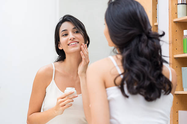 Woman applying moisturizer Woman caring of her beautiful skin on the face standing near mirror in the bathroom. Beautiful young woman applying moisturizer on her face. Smiling girl holding little jar of skin cream and applying lotion on face. routine stock pictures, royalty-free photos & images