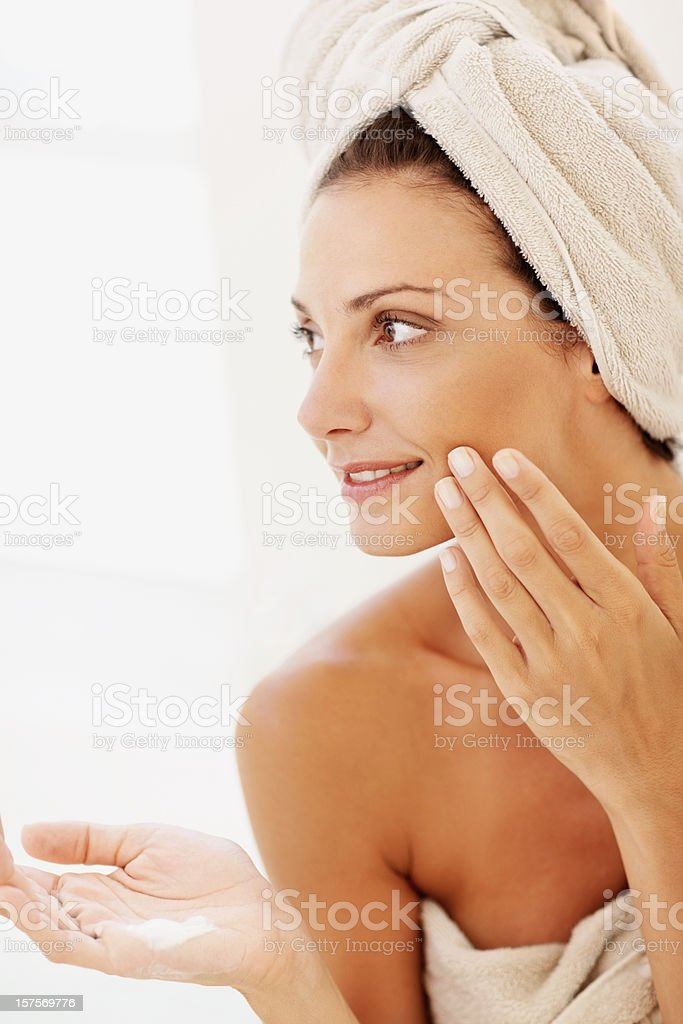 Woman applying moisturizer to her face after shower royalty-free stock photo