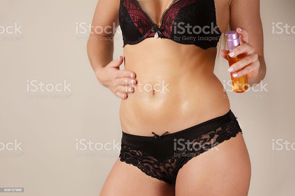 Woman applying moisturizing body oil lotion stock photo