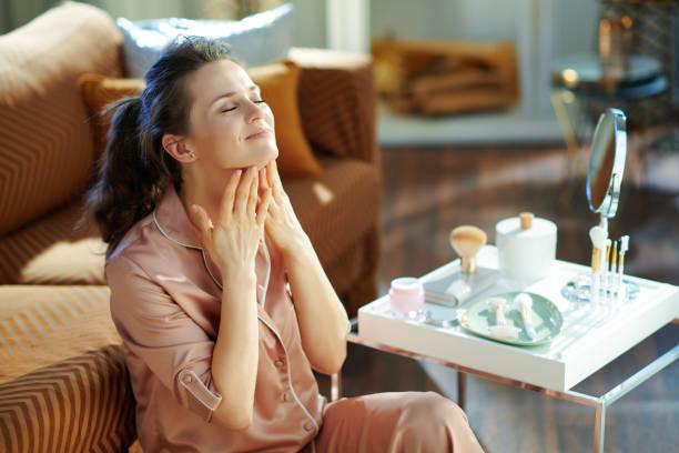 Frau, die Halscreme im modernen Haus am sonnigen Wintertag aufbringt – Foto