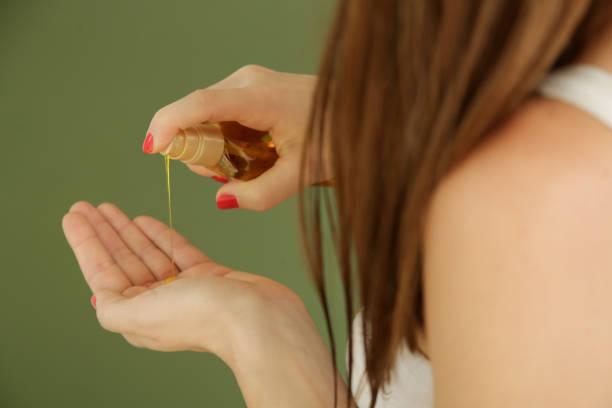 Frau, die Öl auf Haarenden, gespaltene Haarspitzen, trockenes Haar oder Sonnenschutzkonzept aufbringt – Foto