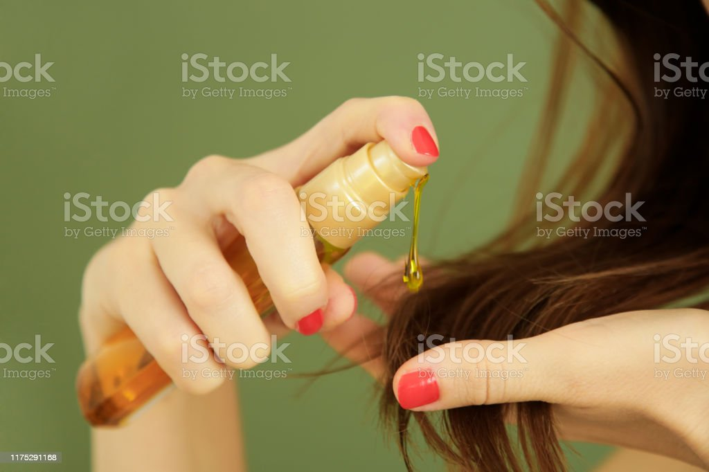 Woman applying oil on hair ends, split hair tips, dry hair or sun protection concept Woman applying oil on hair ends, split hair tips, dry hair or sun protection concept Adult Stock Photo