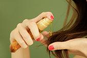 Woman applying oil on hair ends, split hair tips, dry hair or sun protection concept