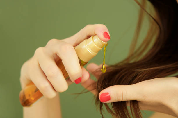 Woman applying oil on hair ends, split hair tips, dry hair or sun protection concept Woman applying oil on hair ends, split hair tips, dry hair or sun protection concept hair stock pictures, royalty-free photos & images