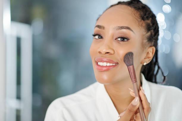 Woman applying peach blush stock photo