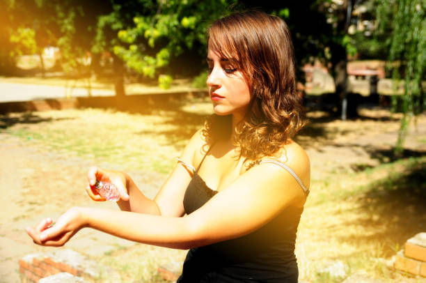 Mulher aplicar perfume no parque - foto de acervo