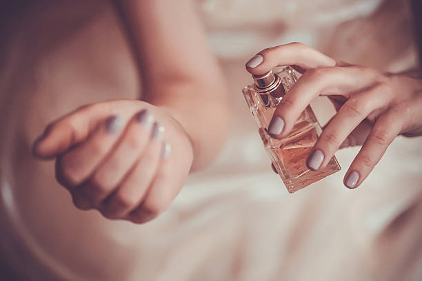 woman applying perfume on her wrist - scented stock photos and pictures