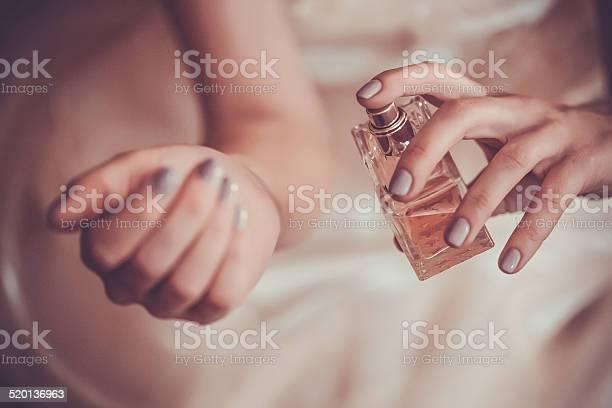 bride applying perfume on her wrist