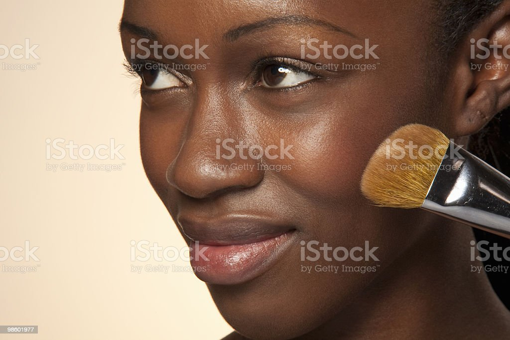 Woman applying powder on chick, looking up smiling royalty-free stock photo