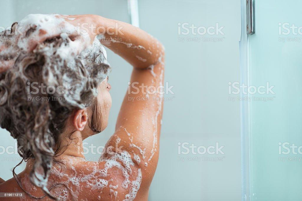 woman applying shampoo in shower. rear view stock photo