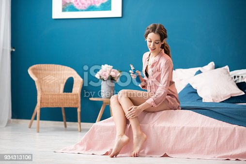 istock Woman applying skin lotion indoors 934313106