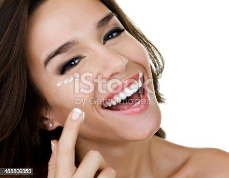 istock Woman applying skin lotion 488806353