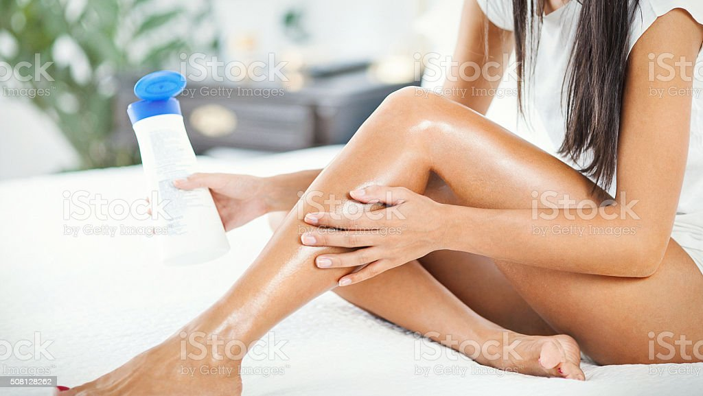 Woman applying some lotion onto her legs. stock photo