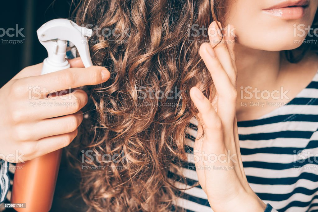 Woman applying spray on curly brown hair royalty-free stock photo