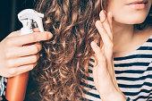 女性の巻き髪を茶色のスプレーを適用します。