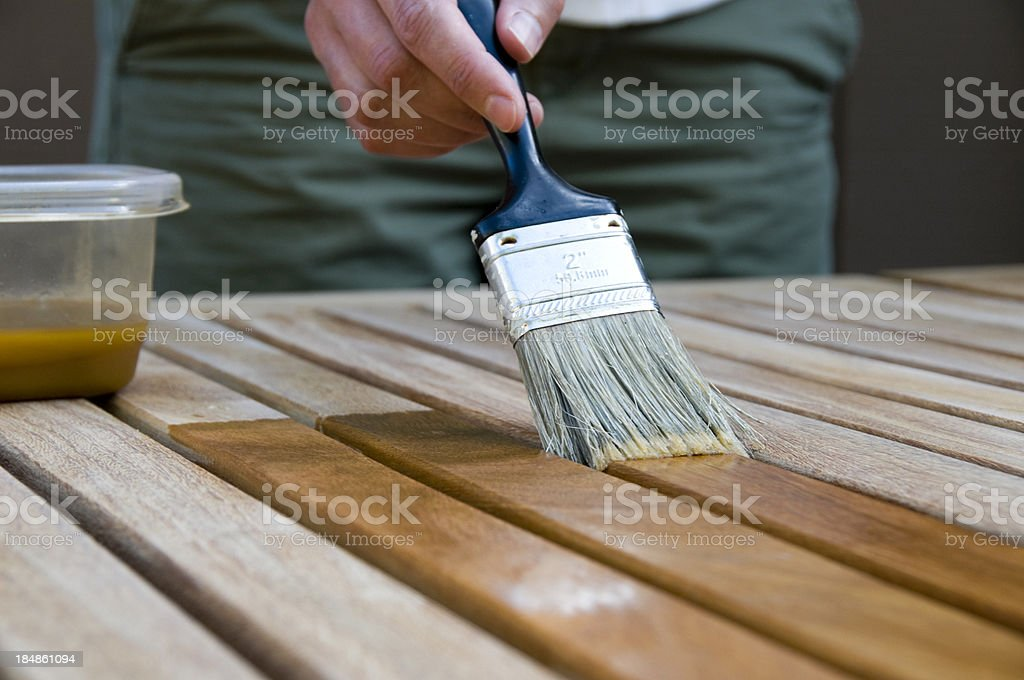 Woman Applying Stain to Wood stock photo