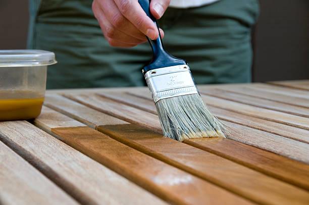 woman applying stain to wood - houtbeits stockfoto's en -beelden