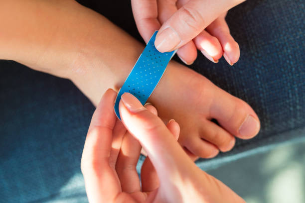 Woman applying sticking plaster to little child's foot; close up view stock photo