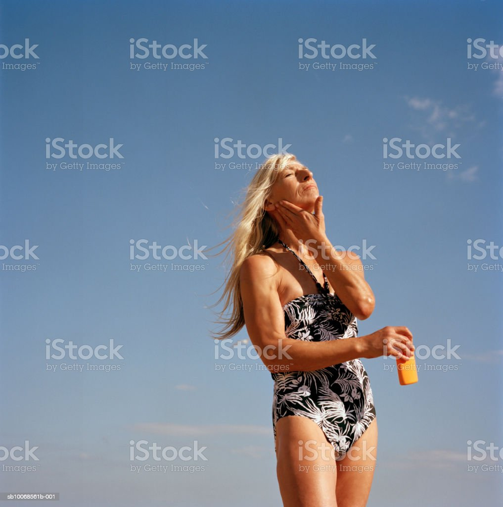 Woman applying sun lotion, against blue sky foto royalty-free