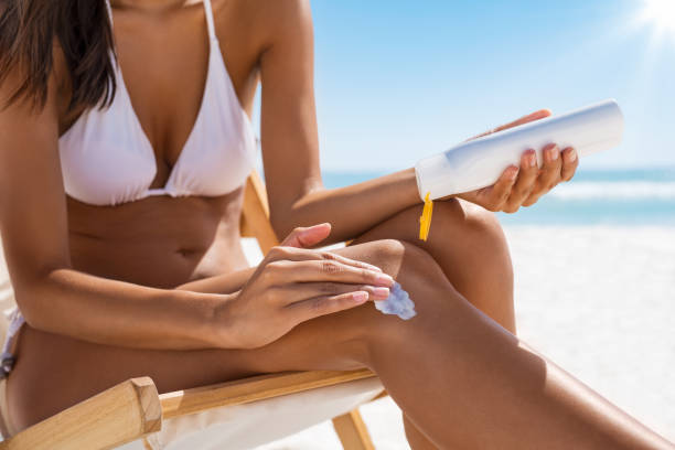 Woman applying sun screen Closeup of woman applying suntan lotion on leg. Closeup of woman hand applying sunscreen cream while sitting on deckchair. Detail of young woman in white bikini applying suntan protection cream. suntan lotion stock pictures, royalty-free photos & images