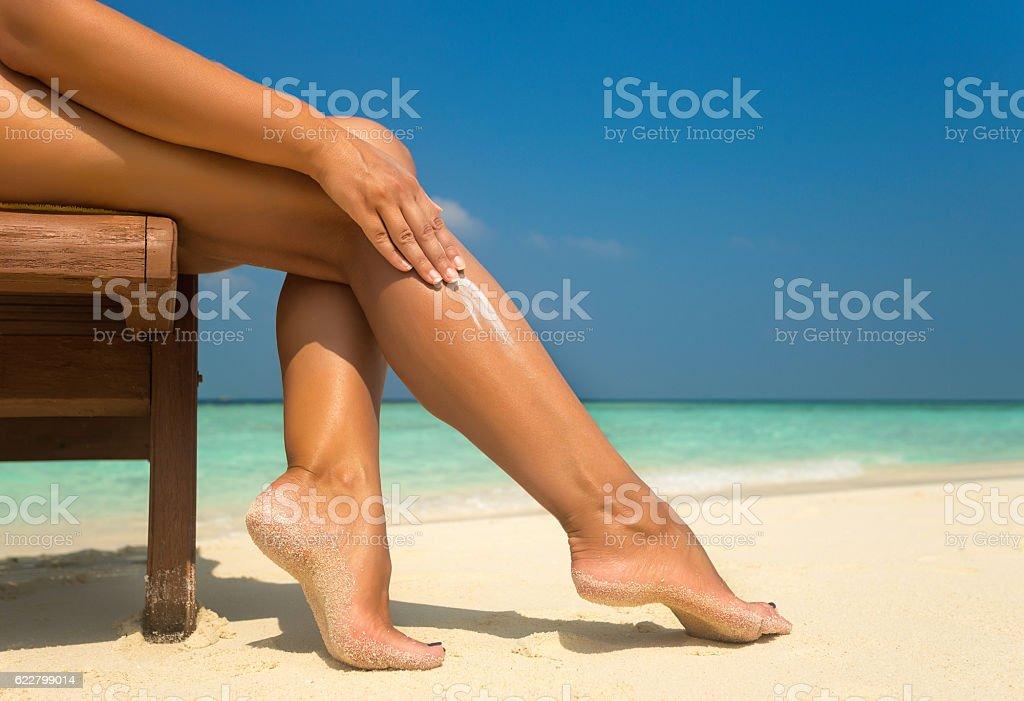 Woman applying sunblock cream on leg on beautiful tropical beach stock photo