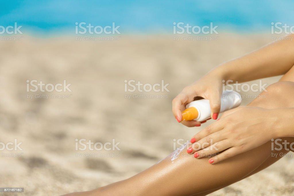 Woman applying sunscreen lotion at a beach stock photo