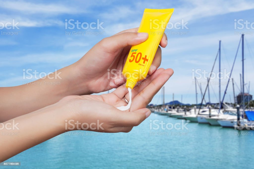 woman applying sunscreen on her hand with blur boats docked at the yacht club background. SPF sunblock protection concept. Travel vacation stock photo
