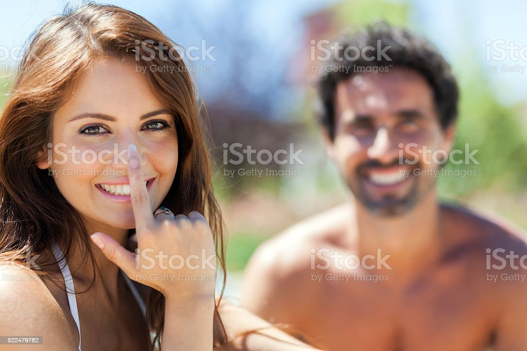 Woman applying sunscreen on her nose stock photo