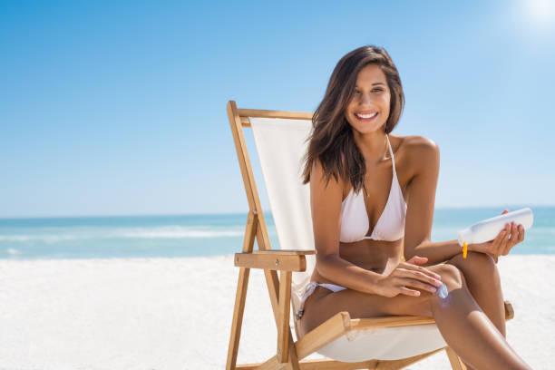 塗抹防曬霜的女人 - 膝蓋以上 個照片及圖片檔
