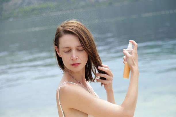Frau Sonnenschutz Spray anwenden, am Strand, Haar-Pflege-Schutzkonzept – Foto