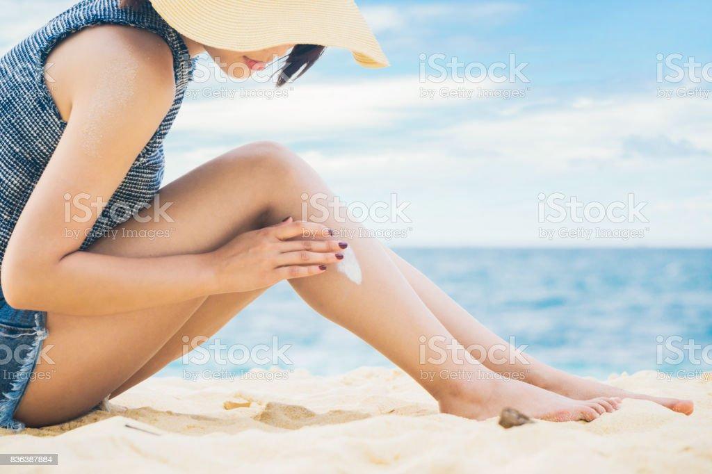 Aplicar protector solar a las piernas de la mujer - foto de stock