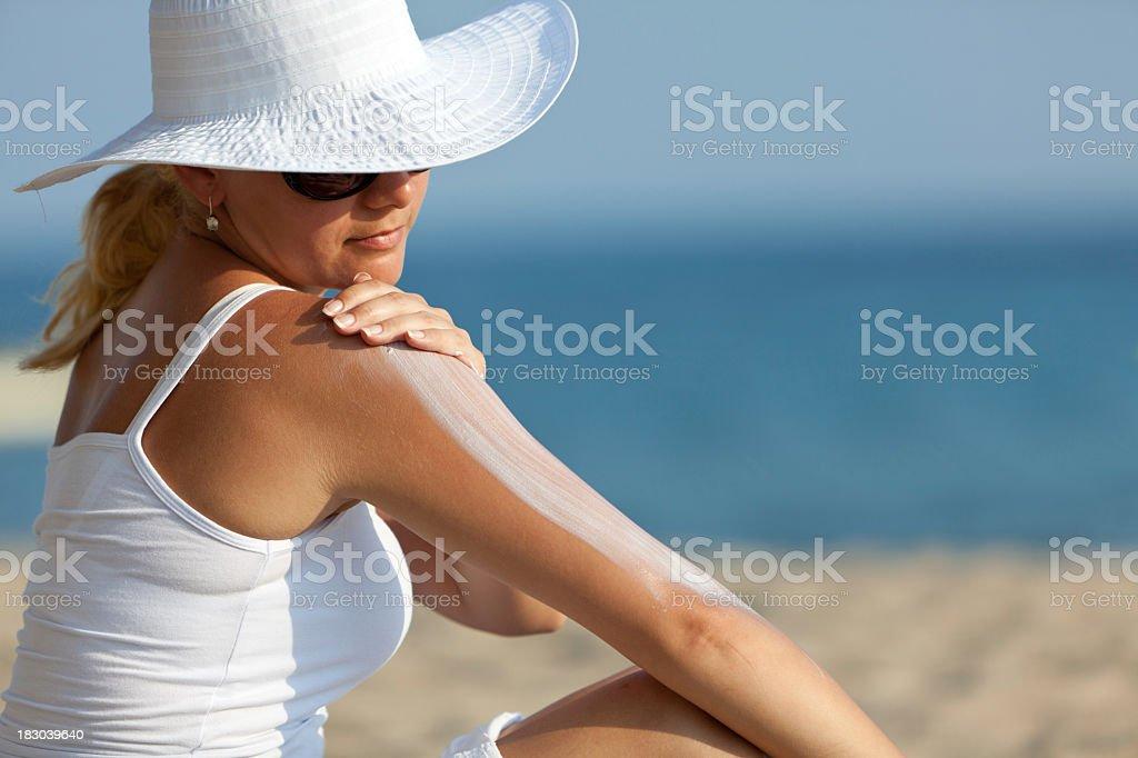 Mujer aplicar crema de sol en la playa - foto de stock