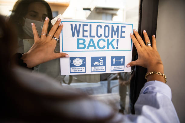 """Woman applying """"Welcome Back"""" sign to the school entrance stock photo"""