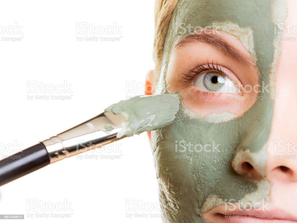 Mujer Aplicación con cepillo máscara facial de arcilla su barro - foto de stock