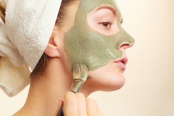 kobieta zastosowanie gliny błoto maski z szczotka do jej twarz - glina zdjęcia i obrazy z banku zdjęć