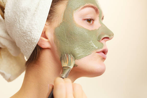 Woman applying with brush clay mud mask to her face Skin care. Woman applying with brush clay mud mask to her face. Girl taking care of oily complexion. Beauty treatment. clay stock pictures, royalty-free photos & images