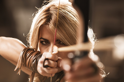 Woman Archer Aiming With Bow And Arrow Stock Photo - Download Image Now