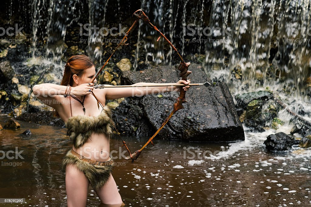 woman archer shoots bow on background waterfall stock photo