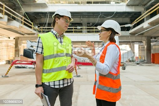 1129095769 istock photo Woman architect and man builder at a construction site. Building, development, teamwork and people concept 1028669204